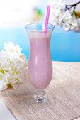 Milk shake on table on light blue background — Stock Photo