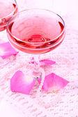 Σύνθεση με ροζ λάμψη κρασί σε ποτήρια και ροδοπέταλα απομονωθεί σε λευκό — Φωτογραφία Αρχείου