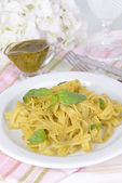 Delicious pasta with pesto on plate on table close-up — Stock Photo