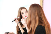 Young beautiful woman making make-up near mirror — Stock Photo