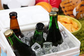 Ice chest full of drinks in bottles on color carpet background — Stock Photo