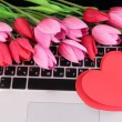 Red hearts and flowers on computer keyboard close up — Stock Photo #43070927