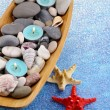 Wooden bowl with Spa stones, sea shells and candles on color background — Stock Photo #43071737