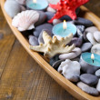 Wooden bowl with Spa stones, sea shells and candles on wooden background — Stock Photo #43071741