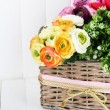 Beautiful flowers in wicker basket, on color wooden background — Stock Photo