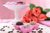 Set of chocolate candies on table on pink background — Stock Photo