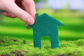 Little paper house in hand on green grass on bright background — Stockfoto