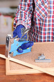 Fastening wooden lath and cork board using construction stapler on bright background — Stok fotoğraf