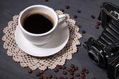 Koffiekopje, vintage camera en oude foto's in het lege, op houten achtergrond — Stockfoto