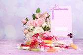 Tasty candies with flowers and card on table on bright background — Zdjęcie stockowe