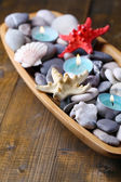 Wooden bowl with Spa stones, sea shells and candles on wooden background — Stock Photo