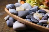 Wooden bowl with spa stones and candles on wooden background — Stock Photo