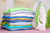 Iron and pile of colorful clothes on table on bright background — Stock Photo