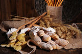 Bread sticks on sackcloth on wooden background — Stock Photo