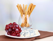 Cheese, grape and bread sticks on plate on wooden table, on light background — Stock Photo