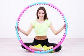 Woman doing exercises with hula hoop in room — Stock Photo