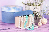 Decorative boxes with beads and flowers on table on bright background — Stock Photo