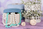 Decorative boxes with beads and flowers on table on bright background — Stockfoto