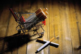 Cigarettes in shopping cart on wooden table on dark background — Stock Photo