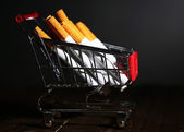 Cigarettes in shopping cart on wooden table on dark gray background — Stock Photo
