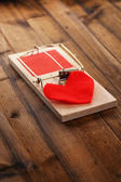 Mousetrap with heart on wooden background — Stock Photo