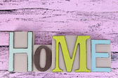 Decorative letters forming word HOME on wooden background — Stock Photo