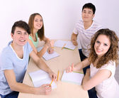Group of young students sitting in room — Stock Photo