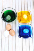 Bowls with paint for Easter eggs and eggs on wooden table — Stockfoto