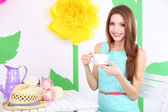 Beautiful young woman sitting on chair at table on decorative background — Stock Photo