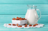 Almond milk in jug with almonds in bowl, on color wooden background — Foto Stock
