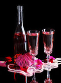 Composition with pink  wine in glasses, bottle  and  roses isolated on black background — Stock Photo