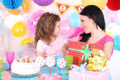 Pretty little girl with mom celebrate her birthday — Zdjęcie stockowe