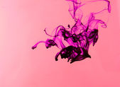 Ink in water on pink background — Stock Photo