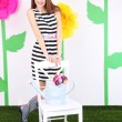 Beautiful young woman with chair on decorative background — Stock Photo
