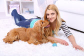 Beautiful young woman with cocker spaniel in room — Stock Photo