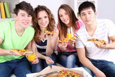 Group of young friends eating pizza in living-room on sofa — Stock Photo
