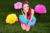 Belle jeune femme en petite jupe avec des fleurs sur l'herbe — Photo