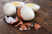 Peeled boiled egg on wooden background — Photo