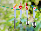 Cutlery dried on rope on natural background — Stock Photo