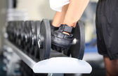 Guy with dumbbells on gym background close-up — Stock Photo