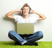 カーペットでリラックスと灰色の壁の背景の音楽を聴く若い男 — ストック写真