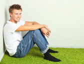 Young man relaxing on carpet, on gray wall background — Foto Stock