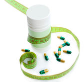 Measuring tape and pills, isolated on white. Dieting concept — Stock Photo