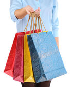 Mladá žena drží v ruce, izolované na bílém barevné nákupní tašky — Stock fotografie