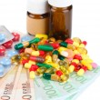 Prescription drugs on money background representing rising health care costs. Isolated on white — Stock Photo #43204603
