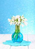 Beautiful snowdrops in vase, on wooden table on bright background — Foto Stock