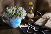 Composition with beautiful snowdrops in vase, candle, old letters and photos on wooden table on sackcloth background — Stock Photo