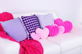 Pink heart shaped pillows, plaid on white sofa — Stock Photo