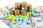 Prescription drugs on money background representing rising health care costs. Isolated on white — Stock Photo