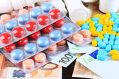 Prescription drugs on money background representing rising health care costs. On wooden background — Foto de Stock